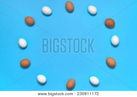 Frame Of White And Brown Eggs On Blue Background, Copy Space. Healthy Food Concept. Top View, Flat L