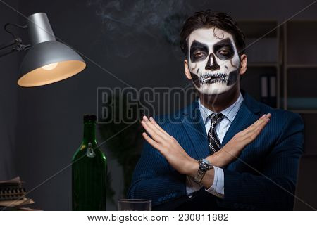 Businessman with scary face mask working late in office