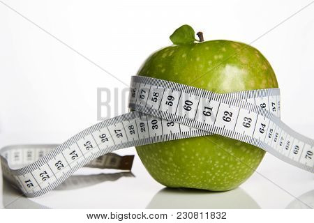 Green Apple And Measuring Tape Measured The Meter On A White Background, Close-up. Healthy Lifestyle