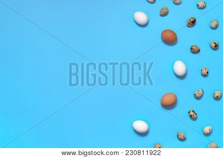 Border Of White, Brown And Quial Eggs On Blue Background, Copy Space. Healthy Food Concept. Top View