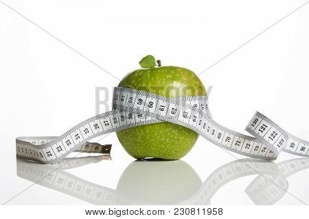 Green Apple With Measuring Tape On White Background, Close-up. Healthy Lifestyle, Diet And Weight Lo