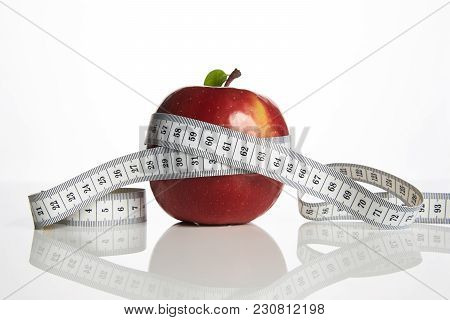 Red Apple With Measuring Tape On White Background, Close-up. Healthy Lifestyle, Diet And Weight Loss
