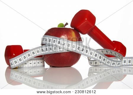 Red Dumbbells, Fresh Red Apple And White Measuring Tape On A White Background, Close-up. Healthy Lif