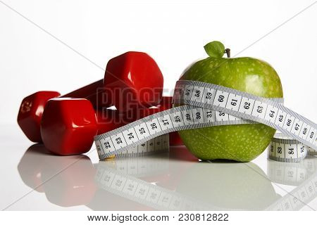 Fresh Appetizing Green Apple And Red Colored Dumbbells Tied With A Measuring Tape On White Backgroun