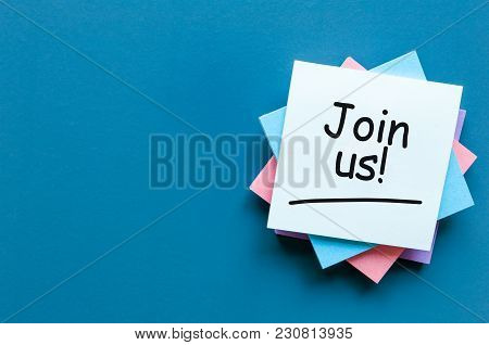 Join Us Sign On Wooden Cubes On Pile Of Papers For Notes At Blue Background.