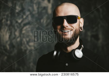 Close-up portrait of a bearded hipster man wearing sunglasses and headphones with piercing in the ears and lips. Studio shot over grunge background.