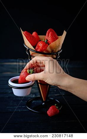 Woman Hand Dipping A Strawberry Into Chocolate. Strawberries In A Fancy Support, Isolated On The Dar