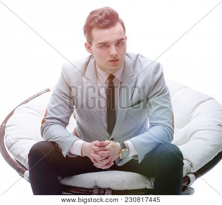 tired businessman sitting in a round chair made of rattan