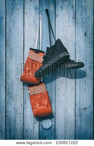 Black Textile Worn Sneakers And Red Leather Boxing Gloves Hanging On A Blue Wooden Wall, Vintage Ton