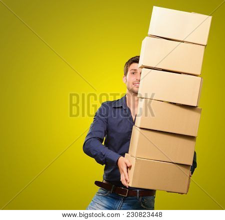 Young Man Holding Stack Of Cardboxes On Coloured Background