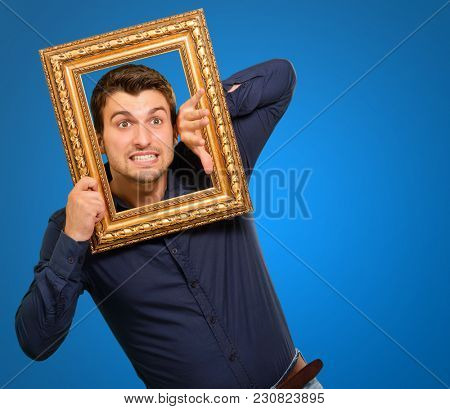 Young Man Holding Picture Frame Isolated On Blue Background