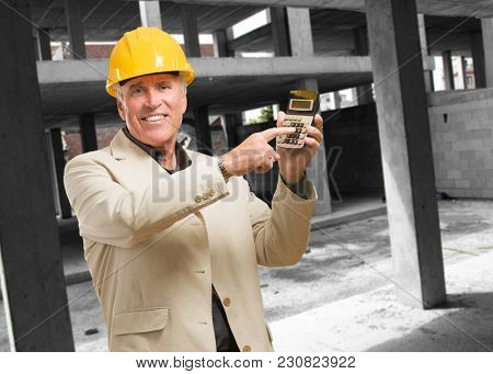 Mature Man With Hard Hat And Calculator at an unfinished building
