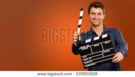 Happy Young Man Holding Clapboard On Coloured Background