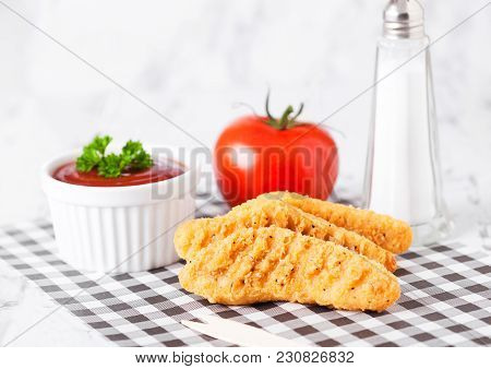 Fried Chicken Dippers On Chopping Board With Sauce And Tomato On Paper Background
