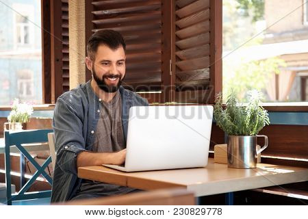 Young blogger using laptop in cafe