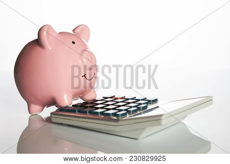 Ceramic Pink Piggy Bank Standing On A Calculator In A Financial, Investment Or Savings Concept Isola