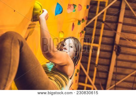 Attractive Young Professional Sport Climber Woman Having Training In The Gym At Artificial Wall.
