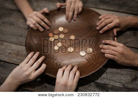 Poor people holding plate with coins on wooden background