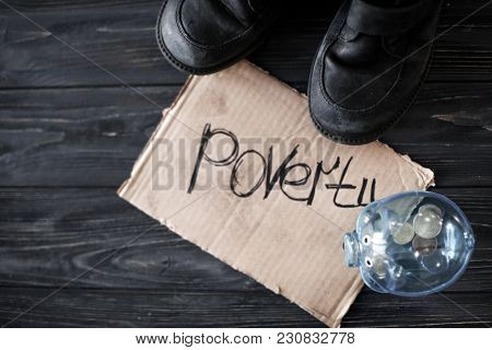 Old shoes, piece of cardboard with word POVERTY and piggy bank on wooden background