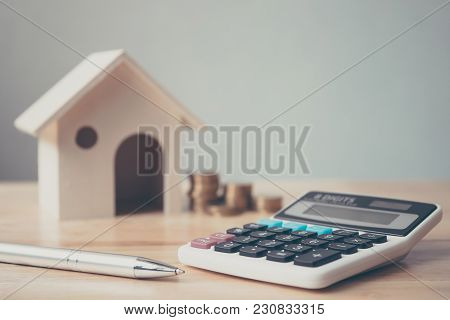 Calculator With Wooden House And Coins Stack And Pen On Wood Table. Property Investment And House Mo