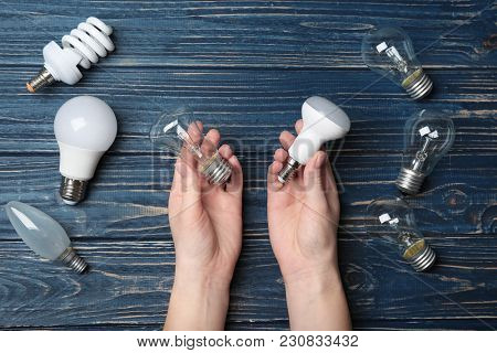 Woman holding LED and incandescent lamp near different light bulbs on wooden background
