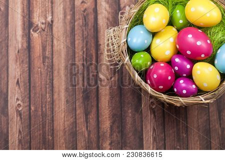 Easter background with colorful Easter eggs in basket on wooden background