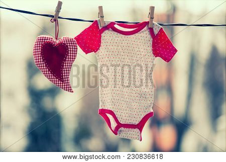 Baby clothes and a red heart hanging on the clothesline