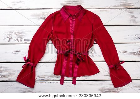 Fancy Red Short Silk Robe. Long Knotted Sleeves. White Wooden Desks Surface Background.