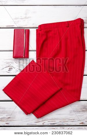 Red Fancy Women Trousers And Wallet. Folded Pants. Bright Wooden Desks Surface Background.