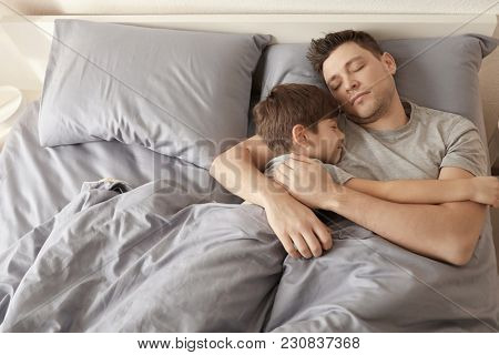 Father with son sleeping in bed at home