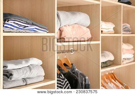 Organized wardrobe closet with clothes