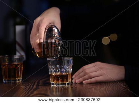 Woman pouring drink into glass at bar, closeup. Alcoholism problem