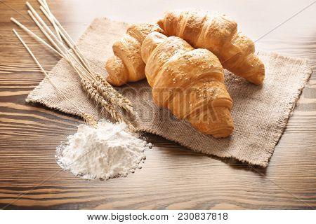 Tasty croissant, spikes and flour on table