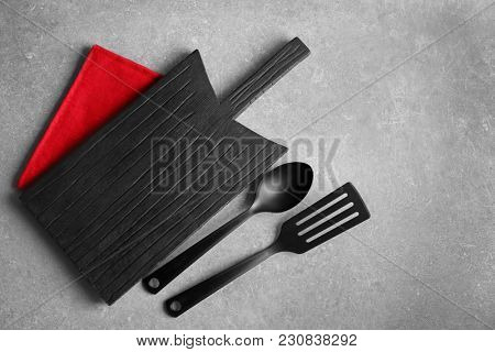 Wooden board, spatula and spoon on grey background. Cooking utensils