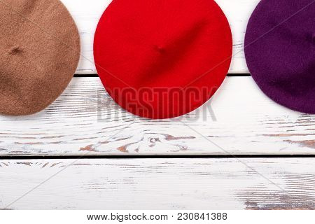 Red Colourful Berets Top View. Flat Lay. White Wooden Background.