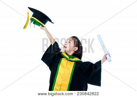 Kindergarten Graduation. Happy Asian Child In Graduation Gown Holding Cap And Diploma Certificate At