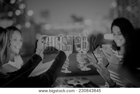 Girl friends having a dinner together at a rooftop bar smartphone technology