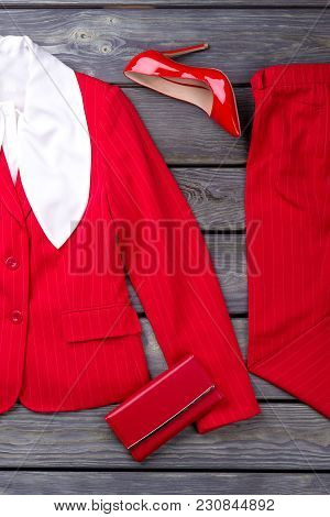 Red Feminine Suit, Shoe And Wallet. Flat Lay, Grey Wooden Surface Background.