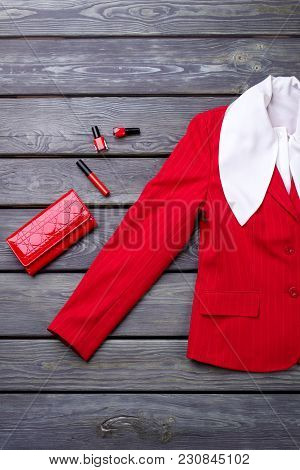 Top View Red Blazer Sleeve And Accessories. Flat Lay, Grey Wooden Surface Background.