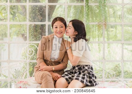 Daughter Pecked Mom On The Cheek And Smilling In The Glass House