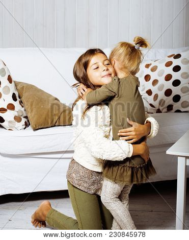 Two Cute Sisters At Home Playing, Little Smiling Girl In House Interior On Sofa, Messing Hair, Fight