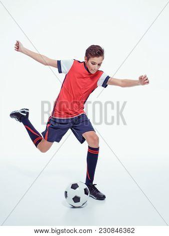 photo young teen boy with soccer ball doing flying kick, studio