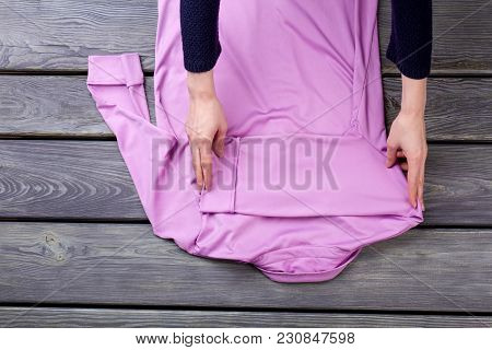 Pink Blouse Folding, Back View. Grey Wooden Surface Background.