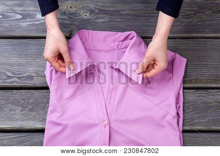 Woman Hands And Pink Shirt Collar. Top View, Flat Lay. Grey Wooden Surface Background.