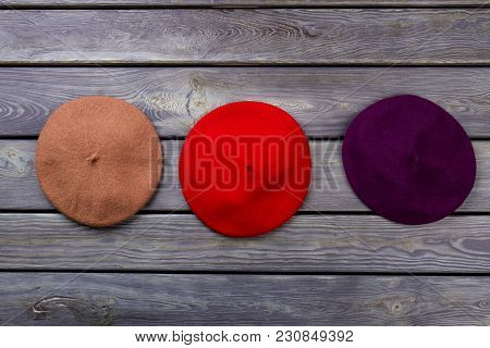 Berete Hats On Wooden Background. Brown, Red And Purple Hats.