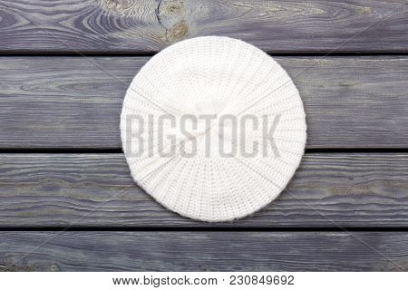 White Wool Knitted Hat, Top View. Flat Lay, Wooden Desk Surface Background.