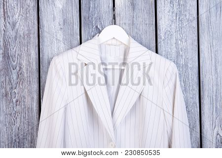 Close Up White Business Jacket On Hanger. Dark Wooden Background. Top View.