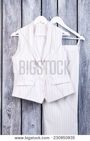 Set Of Striped Business Clothing. White Sleeveless Suit On Hangers. Wooden Surface Background.
