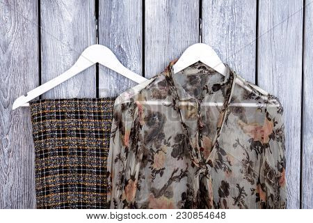 Close Up Stylish Female Apparel On Hangers. Flat Lay, Top View. Grey Desk Surface Background.