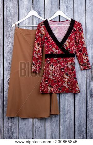Red Kimono On Hanger. Brown Dress Skirt On Hanger. Grey Desk Surface Background.